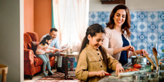 Një familje e lumtur kalon kohë së bashku. Mamaja po gatuan me një nga vajzat. Babai po sheh një album fotografish me vajzën tjetër në dhomën e ndenjjes.