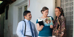 A woman listens as Jehovah's Witnesses offer her the Good News From God! brochure