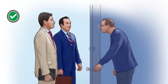 Two brothers quietly stand at the doorstep in the ministry while the householder looks through the peephole