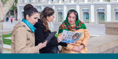 Two publishers offer the Good News brochure to a woman in Azerbaijan