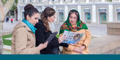 Dos publicadoras ofrecen el folleto Buenas noticias a una mujer en Azerbaiyán