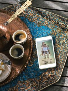 فنجانان من القهوة وإلى جانبهما هاتف تظهر على شاشته الكراسة «الايمان الحقيقي طريقك الى السعادة».