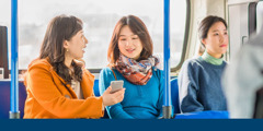 A sister uses an electronic device to informal witness while riding public transportation