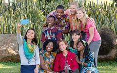 Giovani Testimoni di varie nazionalità indossano vestiti tipici e si fanno una foto