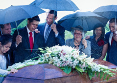 A grieving family surrounds a coffin adorned with flowers