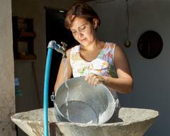 Uma mulher limpando a panela na pia