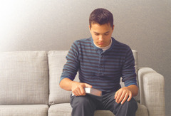 A young brother sits on a sofa and prays