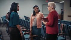 """Unha imaxe do vídeo """"Sucesos futuros que porán aproba anosa valentía"""". Na Sala de Reunións, unha irmá preocupada ecoa mirada perdida despois de ler onde van asignar os predicadores da súa congregación nunha futura fusión con outras congregacións"""