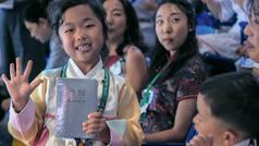Sarong eksena hali sa video na ''An Pagkamuot Dai Nuarin Man Mawawara'! na Internasyonal na mga Kumbensiyon.' Sarong maugmang aking babayi na kapot an saiyang kopya kan 'New World Translation' na naresibi niya.