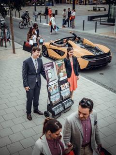 Un matrimonio joven en la predicación pública en una calle con gente comprando y con autos caros.