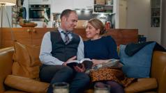 """Scena iz videa """"Uvek pokazuj ljubav u porodici"""". Po povratku sa sastanka, muž i žena kod kuće razgovaraju o jednom biblijskom stihu."""