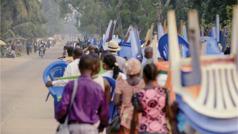 Scena iz videa Ljubav ne prestaje ni... ako nastupi siromaštvo (Kongo). Velika grupa braće i sestara pešači do mesta gde se održava kongres. Mnogi od njih nose stolice i lične stvari.