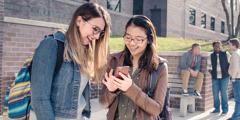 Mlada sestra hrabro svedoči školskoj drugarici i pokazuje joj nešto na mobilnom telefonu.