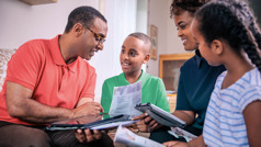 Brat proučava Bibliju sa ženom i decom.