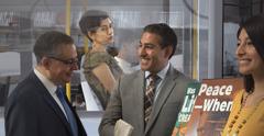 Una sorella inattiva, seduta in un autobus, osserva triste due Testimoni che predicano con un espositore mobile e sorridendo parlano con un uomo.