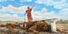 Goliath lying facedown on the ground with a stone in his forehead. David stands over Goliath, holding a sling in one hand and raising his other hand to praise Jehovah.