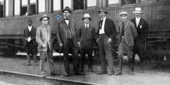 Joseph Rutherford û çend birayên din li ber trenekê disekinin.