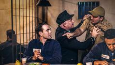 Un gardien de prison retient un policier en colère. Le policier crie après un frère qui est en train de prier.