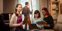 Брат гледа през прозореца на дома си, докато съпругата му и двете им дъщери четат Библията.