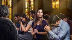 En kvinne i en kirke ser opp mens hun ber, og andre rundt henne sitter med bøyd hode mens de ber.