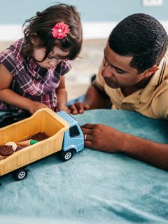 Seorang gadis kecil bermain dengan mainannya, dan ayahnya duduk di sebelahnya.