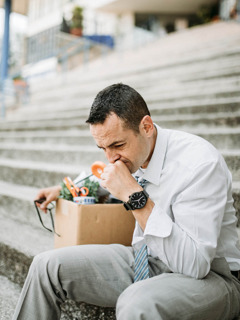 An upset businessman sitting on the steps of a building. A box of personal office items is beside him.