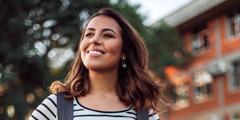 A young woman smiling, looking upward.