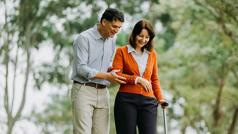 Сімейна пара, яка раніше була в лікарні, тепер гуляє в парку. Чоловік підтримує за руку дружину, яка спирається на ціпок.