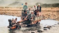 Kathleen, Harvey und andere werden auf einem selbstgebauten Fahrzeug durch einen seichten Fluss gefahren.