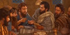 Gesù spezza il pane e lo passa ai suoi apostoli, che sono a tavola con lui.