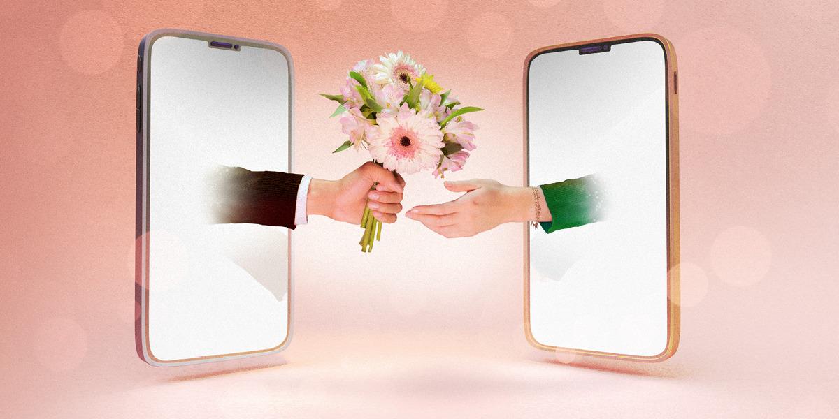 Два мобильных телефона расположены друг напротив друга. Из экрана одного из них протянута мужская рука с букетом, а из другого тянется женская рука.