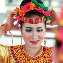 An Indonesian woman puts on a native headdress