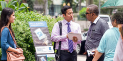 Jehovah's Witnesses stand beside a public witnessing cart in Indonesia and preach to people