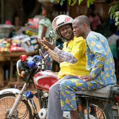 In Benin, Désiré uses an audio player on his motorcycle taxi to preach to a passenger