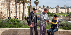 Two of Jehovah's Witnesses in Israel use a tablet to preach to a man