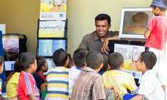 At a literature stand in Suai, Timor-Leste, children watch videos from the series 'Become Jehovah's Friend'