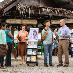 Missionaries Roxanne and Brian stand beside a literature cart near a college campus in Palau and converse with students