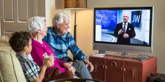 An older couple and a little boy watch a program on JW Broadcasting