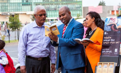 Jehovah's Witnesses stand beside a literature cart in Addis Ababa, Ethiopia, and use Amharic literature to preach to a man