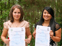 In Honduras, Mirna Paz and Bessy Serrano hold their high school diplomas
