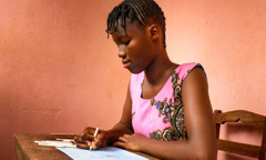 Aminata, a 15-year-old student in Guinea-Bissau, draws a picture of Paradise