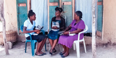 Gérole and her daughter conduct a Bible study with a young girl in Haiti