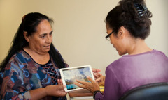 Agnès, a pioneer in New Caledonia, shows her physiotherapist a video