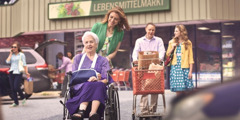 Adult children helping an elderly parent, who is in a wheelchair, with her grocery shopping