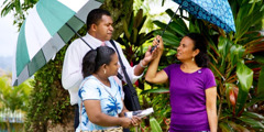 A Jehovah's Witness couple handing a woman an umbrella as they speak with her