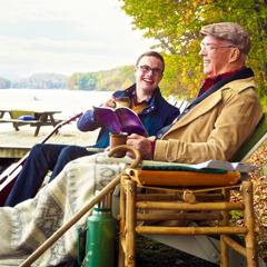 A young brother enjoys time at a lakeside with an elderly brother