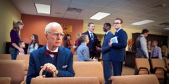 A young brother observes an elderly brother sitting alone in the Kingdom Hall