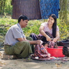 Using a tub of water, a husband helps his wife wash clothes