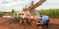Men work together to dig a truck out of the mud