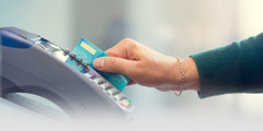 A woman inserts a bank card into an electronic card reader